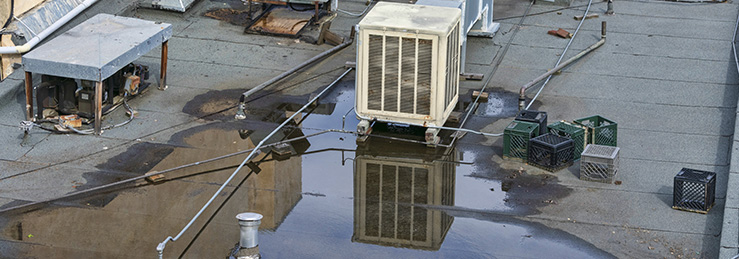 Flat commercial roof with a large puddle of ponding water around rooftop HVAC units.