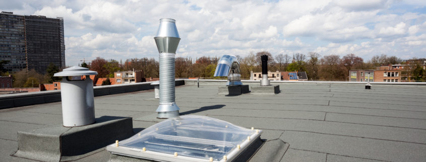 Commercial roof with multiple vents that is protected by roof leak service agreement