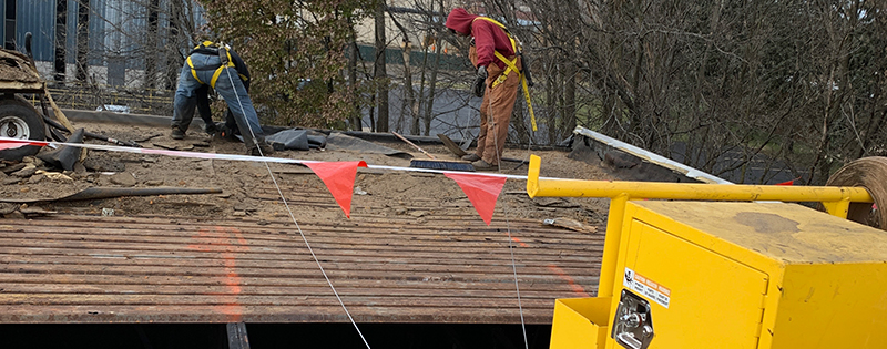 Commercial roofers performing a roof replacement project.
