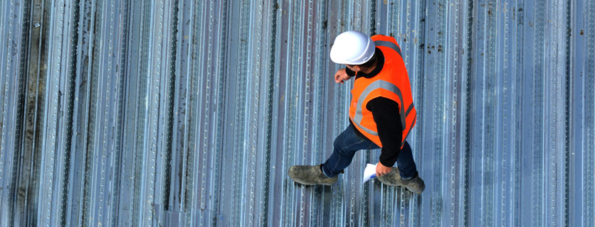 A construction worker walking on commercial roof for cooperative purchasing project.